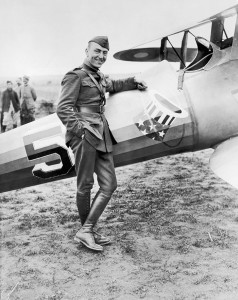 Eddie Rickenbacker, dressed in uniform, stands next to his World War I plane in a field near Toul, France.